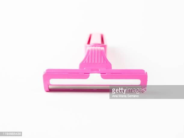 close up of disposable pink razor on a white background - schaamhaar stockfoto's en -beelden