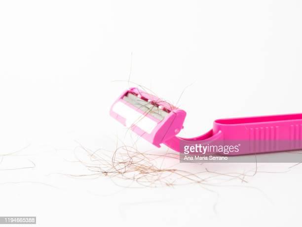 close up of disposable pink razor with hairs between the blades on a white background - schaamhaar stockfoto's en -beelden