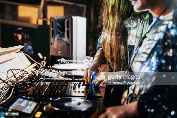 Close Up Of DJs Working The Mixer While Performing At Nightclub