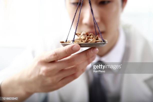 Close up of doctor weighing herbal medicines with scales