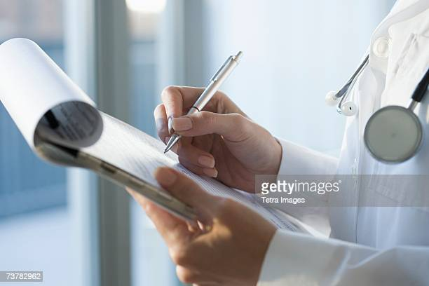 Close up of doctor writing on medical chart