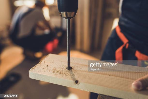 close up of drilling wooden plank at construction site. - drill bit stock photos and pictures