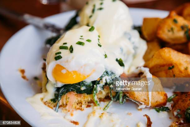 Close up of Eggs Benedict with liquid egg yolk and bechamel sauce, served with potato