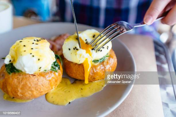 close up of eggs benedict with liquid egg yolk running out - french food stock pictures, royalty-free photos & images
