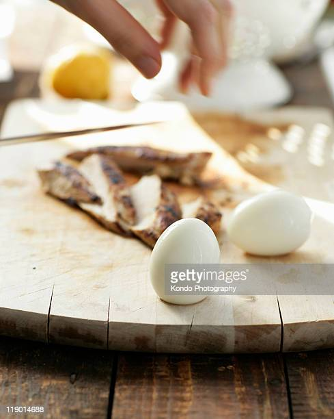 close up of eggs on cutting board - hard boiled eggs stock photos and pictures