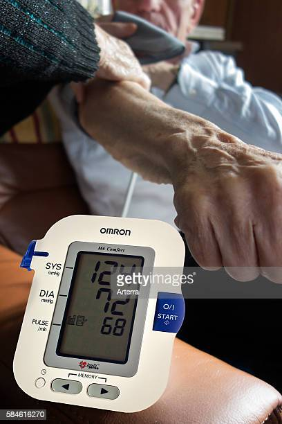 Close up of elderly couple checking their own blood pressure using a digital blood pressure monitor in living room at home