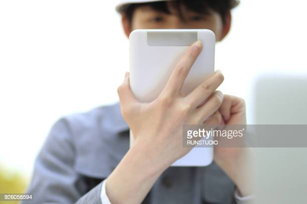 Close up of engineer using digital tablet outdoors