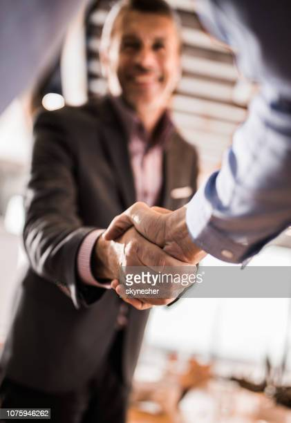 Close up of entrepreneurs shaking hands in the office.