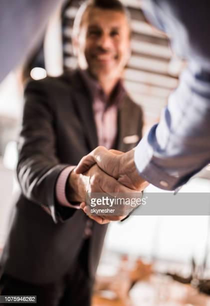 feche de empresários, apertando as mãos no escritório. - vertical - fotografias e filmes do acervo