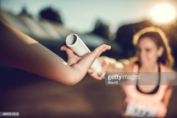 close up of exchanging relay baton on a sports race. - passing sport stockfoto's en -beelden