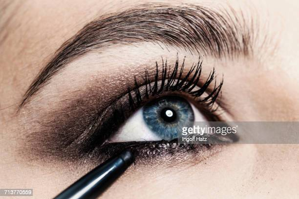 close up of eyeliner being applied to young womans eye - eye make up stock pictures, royalty-free photos & images