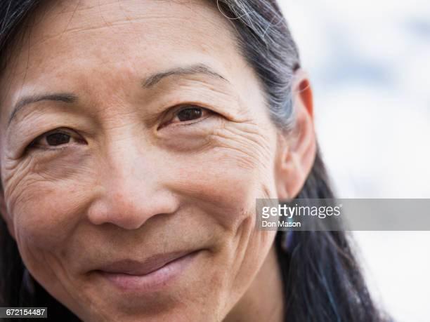 close up of face of smiling japanese woman - solo una donna matura foto e immagini stock