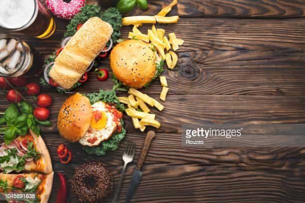 nahaufnahme eines fast-food-snacks und trinken am tisch - schnellimbiss stock-fotos und bilder