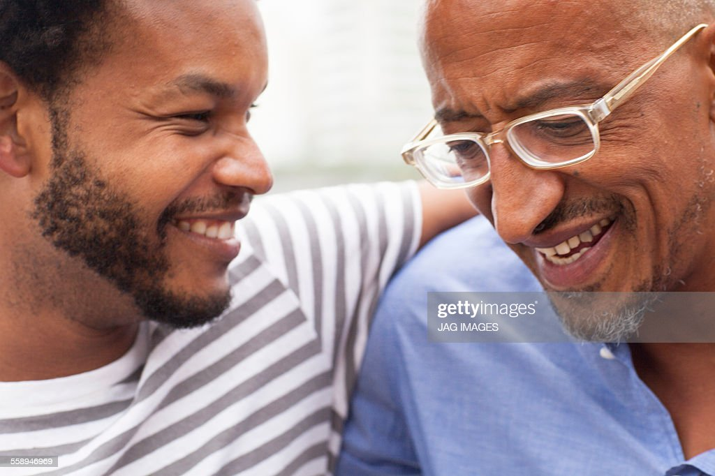 Close up of father and mid adult son on Ipanema Beach, Rio De Janeiro, Brazil : Stock Photo