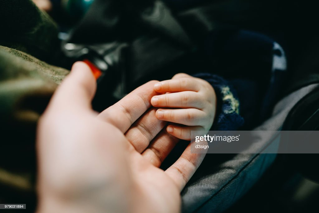 Close up of father holding baby's hand gently : Stock Photo