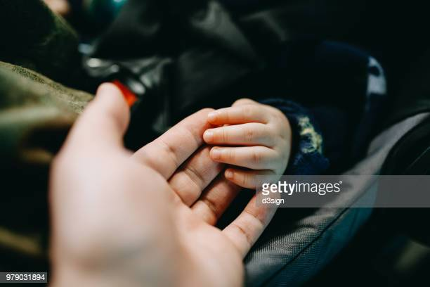 close up of father holding baby's hand gently - baby boys stock pictures, royalty-free photos & images