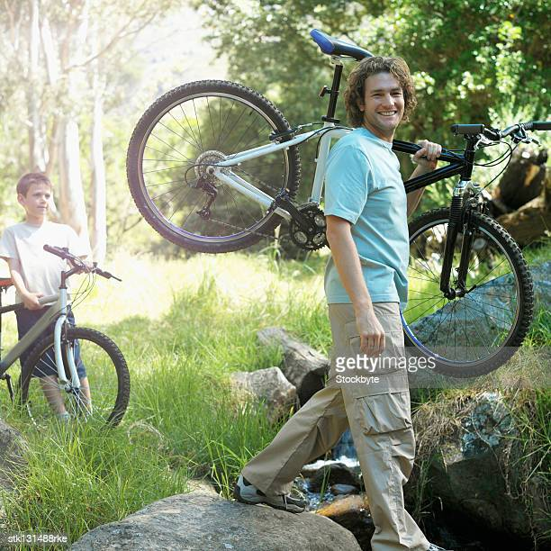 close up of father lifting bicycle and son (8-9) holding bicycle in countryside