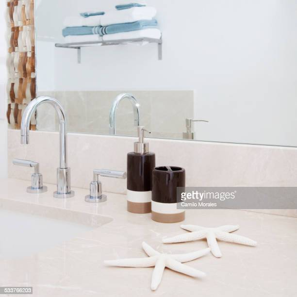Close up of faucet, sink and mirror in modern bathroom