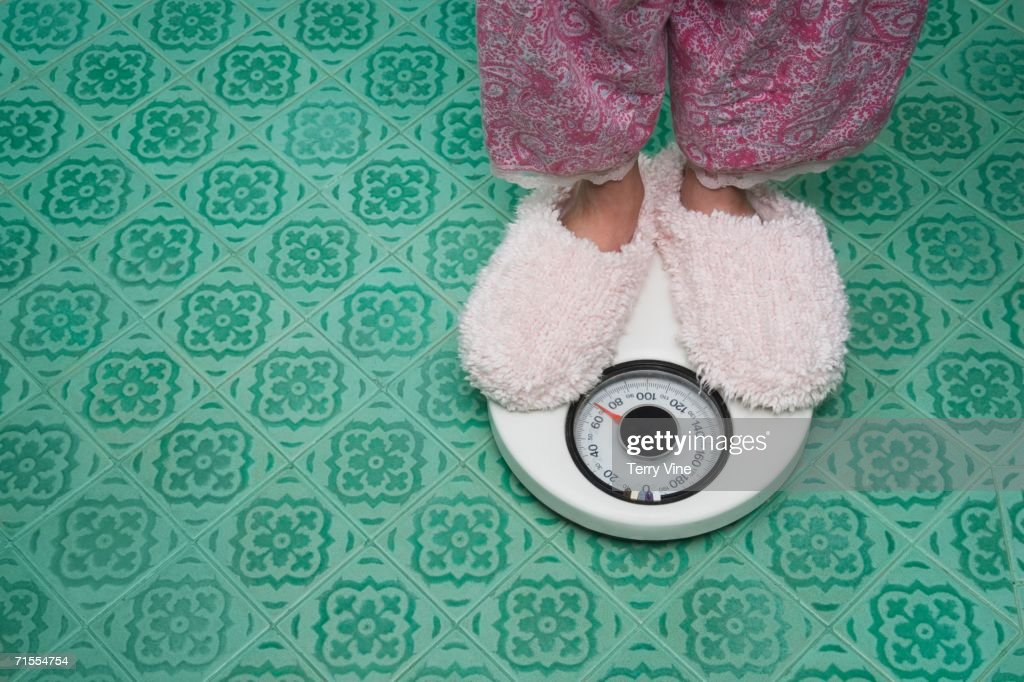 Close up of feet in slippers on bathroom scale : Photo