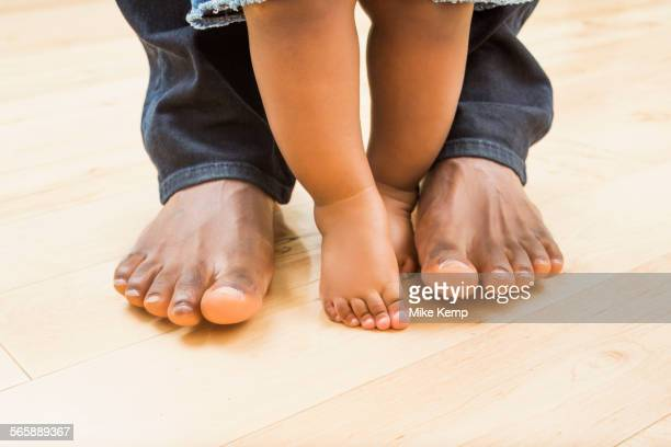 close up of feet of black father and baby son - black men feet stock photos and pictures
