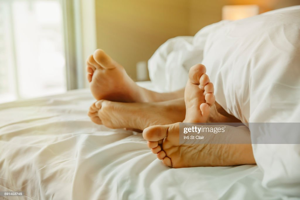 Close up of feet of couple in bed : Stock Photo