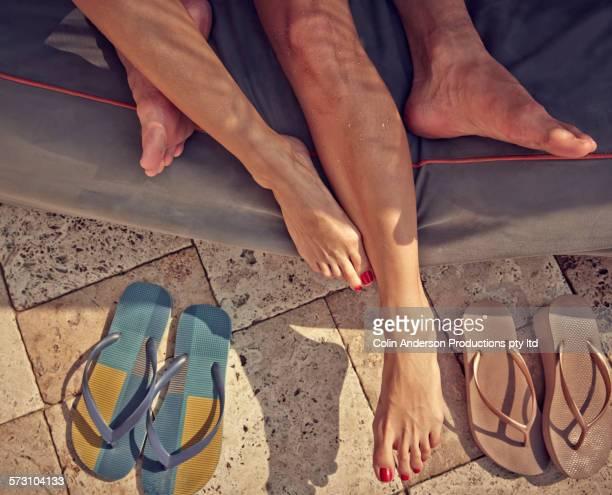 Close up of feet of Hispanic couple laying in cabana