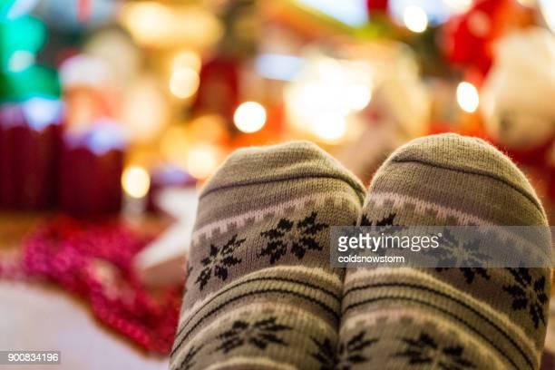 close up of feet wearing warm cozy scandinavian-style christmas socks beneath illuminated christmas tree - dezembro imagens e fotografias de stock