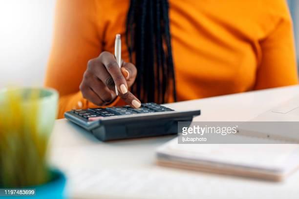 fermez-vous vers le haut de comptable ou de banquier féminin faisant des calculs - ��couter photos et images de collection