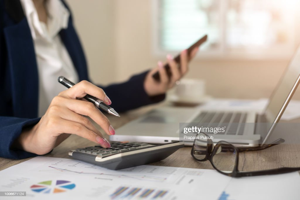 Close up of female accountant or banker making calculations. Savings, finances and economy concept : Stock-Foto