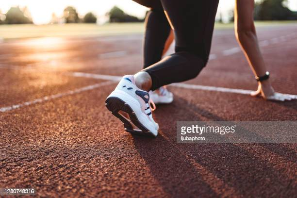 close up of female athlete getting ready to start running on track . focus on sneakers - sprint stock pictures, royalty-free photos & images