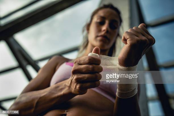close up of female athlete wrapping her wrist in adhesive bandage. - wrist stock pictures, royalty-free photos & images