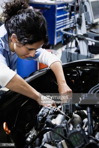 Close up of female auto mechanic working on engine in auto repair shop