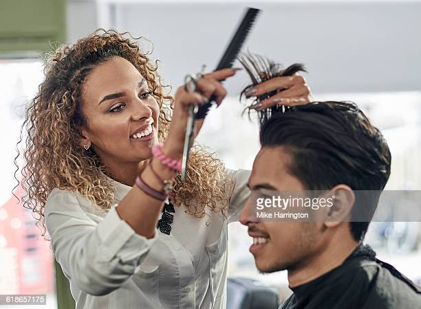 Close up of female barber cutting hair