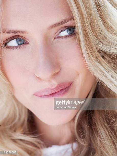 close up of female biting lip, looking to the left - biting lip stock pictures, royalty-free photos & images