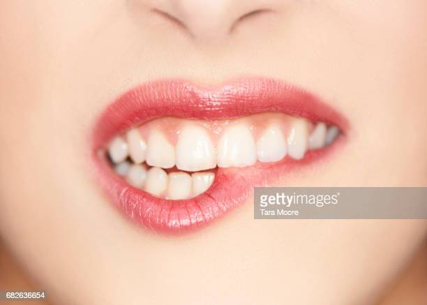 close up of female biting lips - menselijke lippen stockfoto's en -beelden
