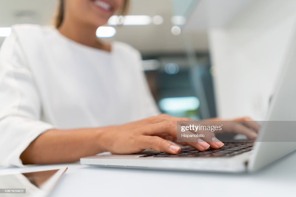 Close up of female businesswoman working on laptop typing something : Stock Photo