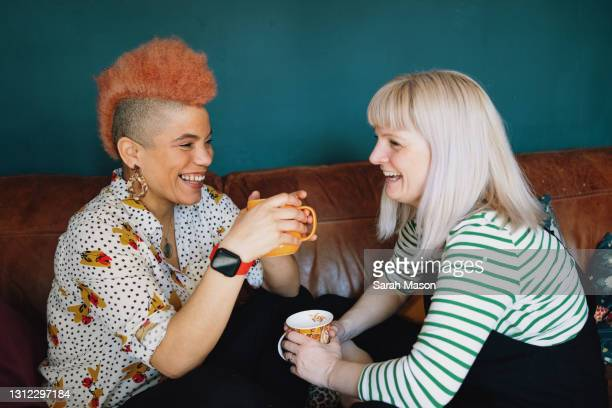 close up of female couple laughing on sofa - human relationship stock pictures, royalty-free photos & images