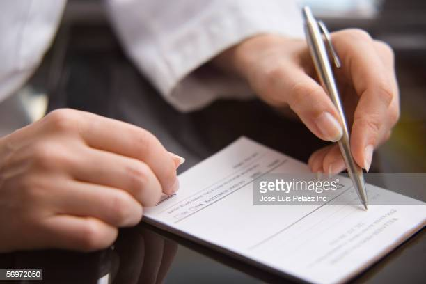 close up of female doctor's hands writing prescription - prescription medicine stock pictures, royalty-free photos & images