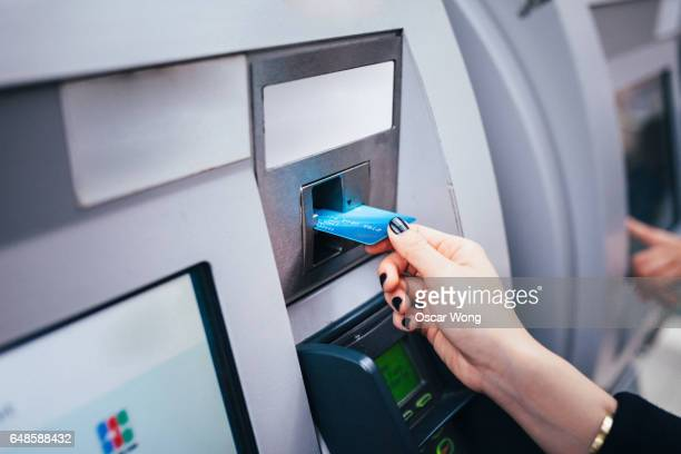 Close up of female hand inserting card to machine