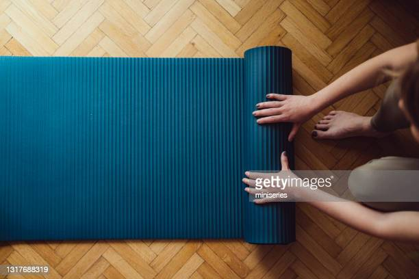 close up of female hands folding blue exercise mat on wooden floor - mat stock pictures, royalty-free photos & images