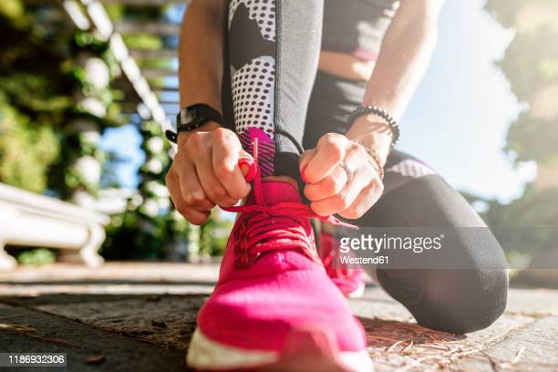 close up of female hands tying pink sneakers - pink shoe stock pictures, royalty-free photos & images