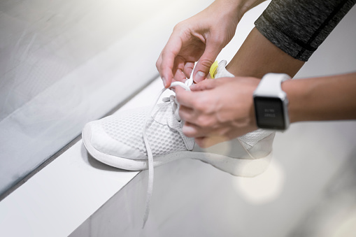 Close up of female hands tying sneakers with smartwatch - gettyimageskorea
