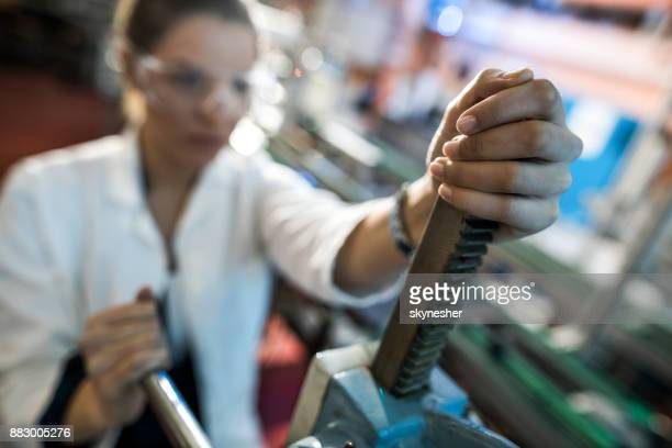 Close up of female lab worker working on a machine.