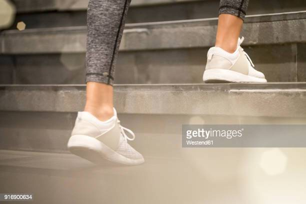 close up of female legs with white sport sneakers running up the stairs - degraus e escadas - fotografias e filmes do acervo