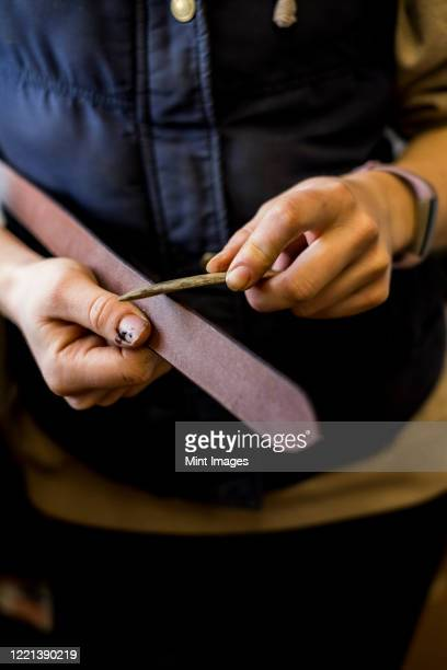 close up of female saddler standing in workshop, working on leather strap. - strap stock pictures, royalty-free photos & images
