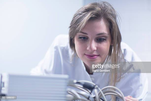 close up of female scientist in lab using scanning electron microscope - sigrid gombert stockfoto's en -beelden