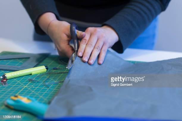close up of female tailor cutting blue fabric with scissors. - sigrid gombert imagens e fotografias de stock