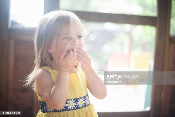 close up of female toddler with hands over mouth - heshphoto photos et images de collection