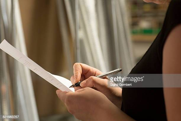 close up of female warehouse worker taking stock in hardware store - sigrid gombert - fotografias e filmes do acervo