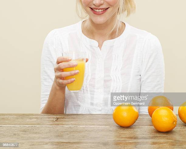close up of female with glass of orange juice
